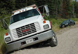 Picture of a white flatbed tow truck assisting a black car that has slid into the ditch