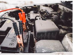Picture of a dead battery with jumper cables hooked up to it.